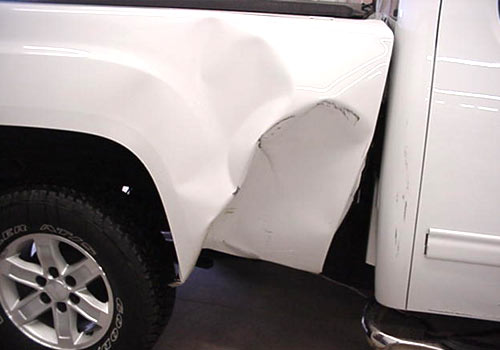 Before photo of a white pickup truck with truck box damage