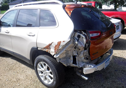 Before photo of a silver SUV with rear-end collision damage
