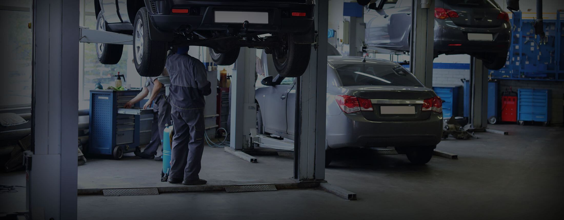 Auto Technicians working on a vehicle raised on an auto lift