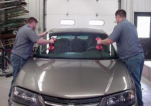 Automotive Technicians from Wayne's Auto Body replacing a windshield in a silver car